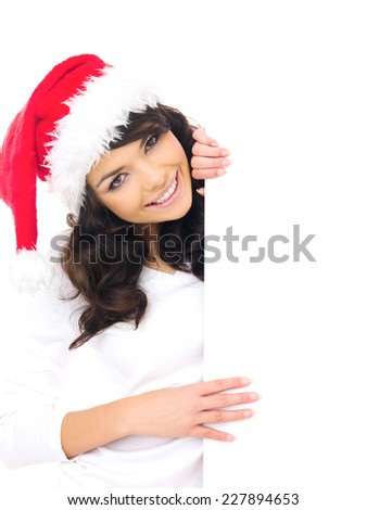 Attractive young woman with a lovely smile in a Santa hat holding the side of a blank white sign or placard with copyspace for your text - stock photo