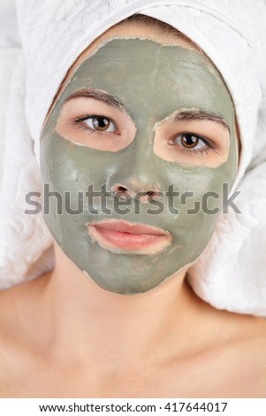 Attractive young woman with applied mud clay mask. Spa beauty procedures skin care treatment concept. White salon towels background - stock photo