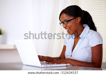 Attractive young woman with black glasses working on laptop at office - copyspace - stock photo