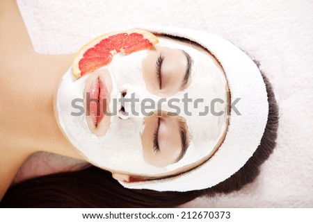 Attractive young woman with fruit mask on a face at spa saloon - stock photo