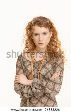 Attractive young woman with long curly hair standing with armes crossed.? - stock photo