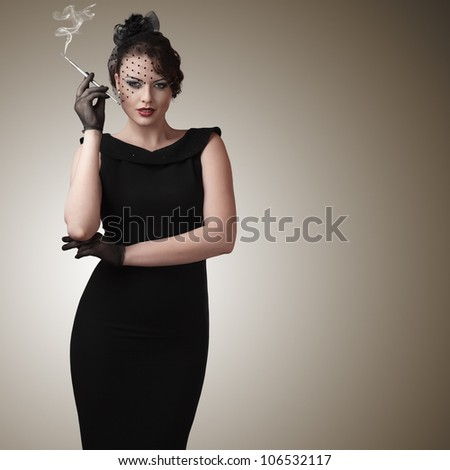 Attractive young woman with slim cigarette retro style portrait - stock photo