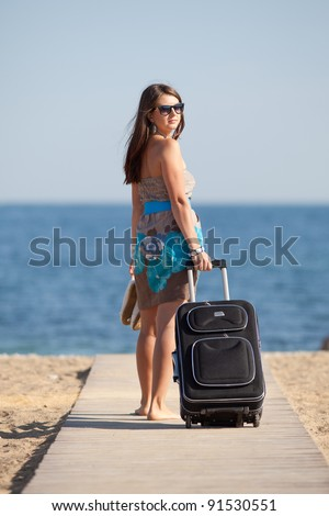 Attractive young woman with suitcase on the beach. Barefoot young woman in dress and sunglasses with rolling suitcase walking along the beach - stock photo