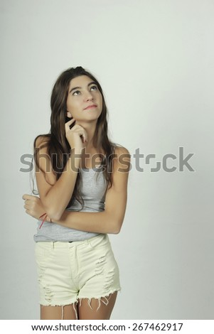 Attractive young woman with thinking expression, isolated on grey background. - stock photo