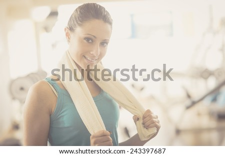 Attractive young woman with towel at gym smiling at camera. - stock photo
