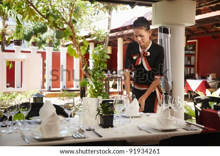 Attractive young woman working as waitress in exclusive restaurant, setting up a table. Waist up, front view - stock photo