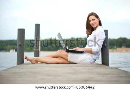 attractive young woman working on laptop at the water - stock photo