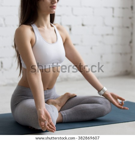 Attractive young woman working out in loft interior, doing yoga exercise on blue mat, Sitting in Ardha Padmasana, Half Lotus Posture, meditating, breathing, closeup - stock photo