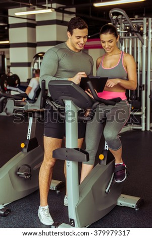 Attractive young woman working out on an exercise bike in gym, muscular trainer consulting her. Both smiling - stock photo