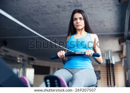 Attractive young woman working out on training simulator at fitness gym - stock photo