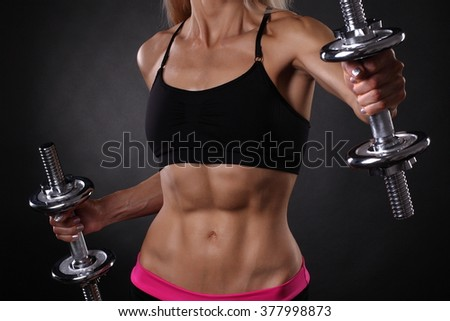 attractive young woman working out with dumbbells - stock photo