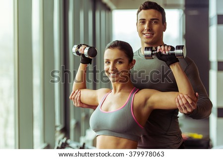 Attractive young woman working out with dumbbells in gym, handsome muscular trainer helping her. Both smiling - stock photo
