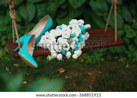 Attributes runaway bride. Wedding bouquet of white roses and blue ribbons and blue patent leather high-heeled shoes - stock photo
