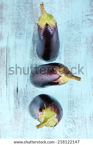 Aubergines on wooden background - stock photo