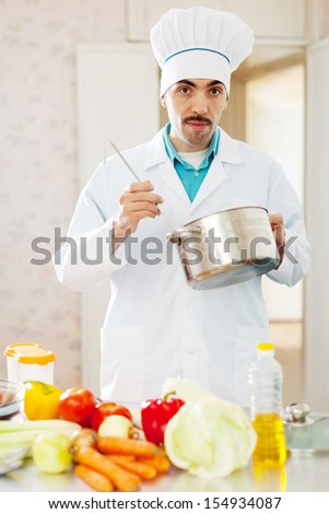 aucasian cook man tasting soup with ladle from pan in kitchen - stock photo