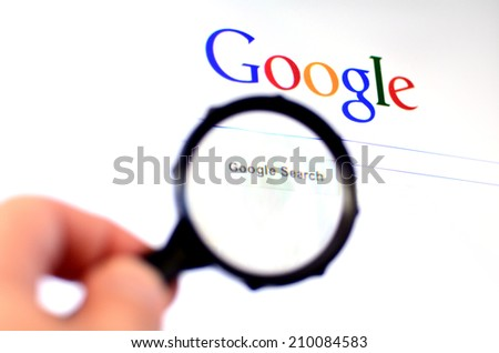 AUCKLAND - AUG 10 2014:Hand holds Magnifying glass against Google homepage.620 million users visit www.google.com daily, almost all the people who use the Internet every day. - stock photo