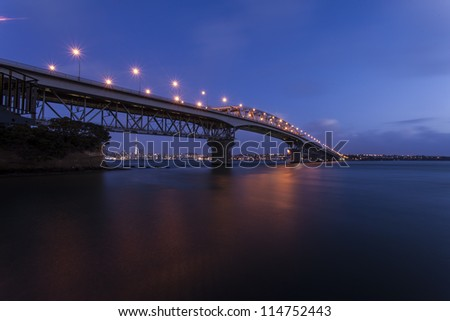 Auckland Harbor Bridge/ Auckland's iconic harbor bridge at dusk with the city lights in the background - stock photo