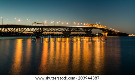 Auckland Harbour Bridge reflecting on the water  - stock photo