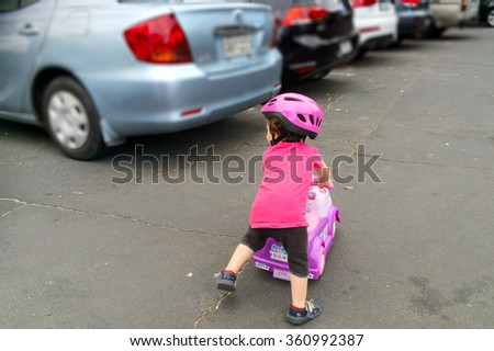 AUCKLAND - JAN 11 2016:Little girl (Naomi Ben-Ari age 1-2) rid a toy car in parking lot. The U.S. Center for Disease Control reported that about 300 fatalities per year result from backup collisions. - stock photo