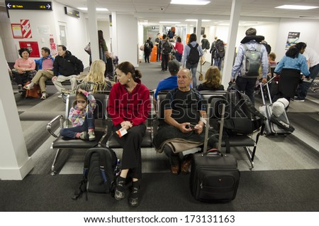AUCKLAND - JAN 12:Passengers waiting to get on plane at Auckland Airport on Jan 12 2014.Only 5% of passengers obtain their boarding pass through the Internet. - stock photo