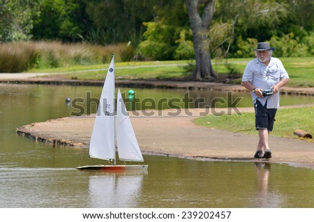 AUCKLAND, NZL - DEC 21 2014: Man sails a remote controlled sailing wooden yacht in a pond.Radio-controlled boats are the most common type of boat amongst casual hobbyists. - stock photo