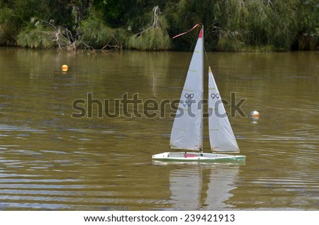 AUCKLAND, NZL - DEC 21 2014:One remote controlled sailing wooden yacht race in a pond.The racing is governed by the same Racing Rules of Sailing that are used for full-sized crewed sailing boats - stock photo