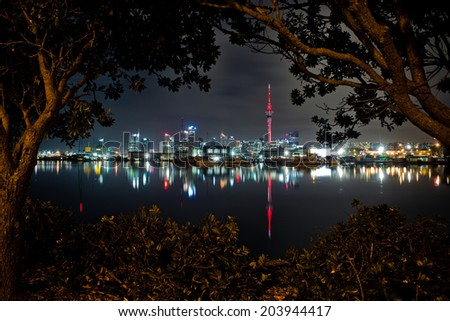 Auckland Skyline reflecting on Westhaven Marina framed by trees  - stock photo