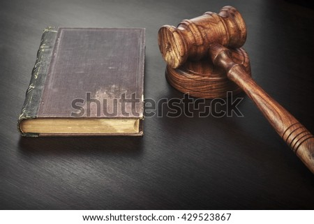 Auctioneers or Judges Hammer or Gavel with Old Book On Black Wooden Background Auction Or Trial Or Law Education Concept - stock photo
