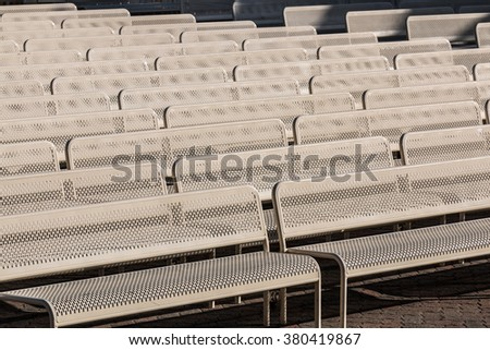 Audience benches lined up in rows facing right. - stock photo