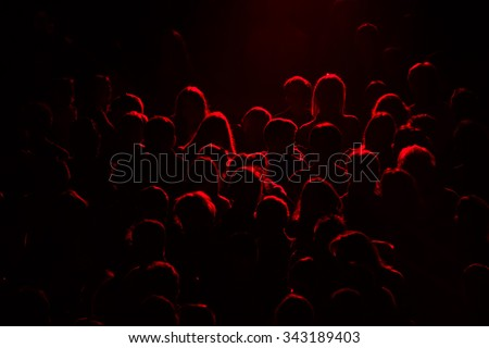 audience silhouette on purple and red light - stock photo