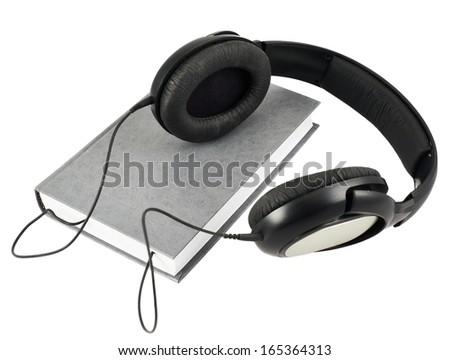 Audio-book concept composition as a headphone set over a book composition isolated over white background - stock photo