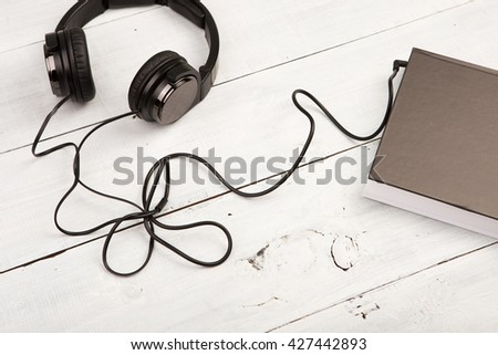 Audio book concept with black book and headphones on white wooden background - stock photo