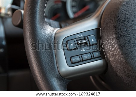 Audio control buttons on the steering wheel of car - stock photo