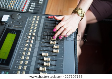Audio mixing console closeup with neat woman's hand - stock photo