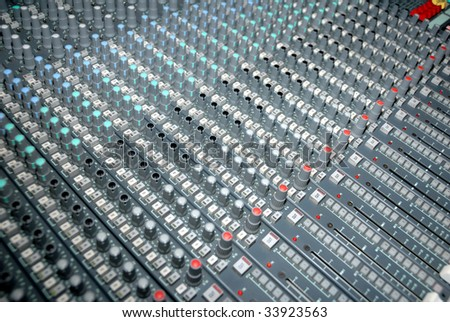 Audio mixing console in a recording studio. Faders and knobs of a sound mixer. - stock photo