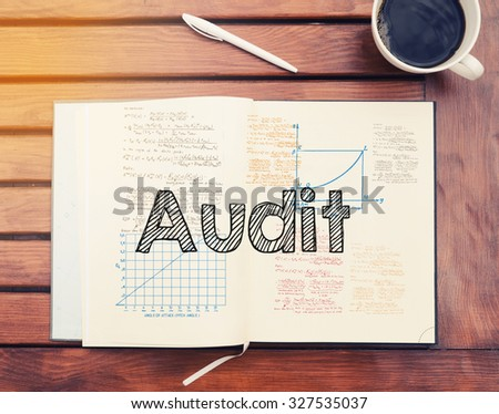 Audit : text inside notebook on table with coffee - stock photo