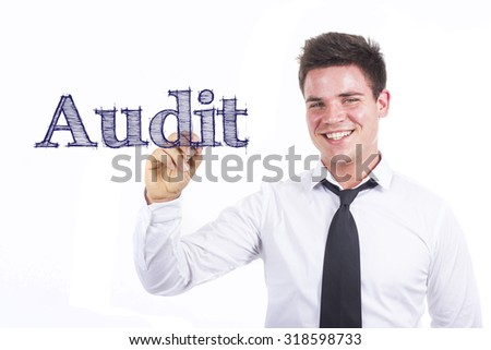 Audit - Young smiling businessman writing on transparent surface - stock photo