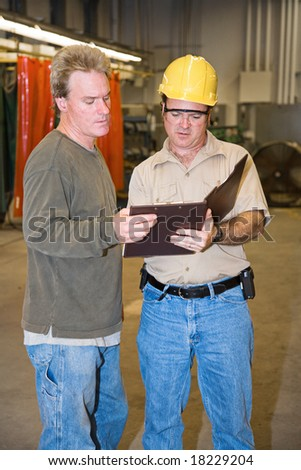 Auditor discussing his report with a factory foreman. - stock photo