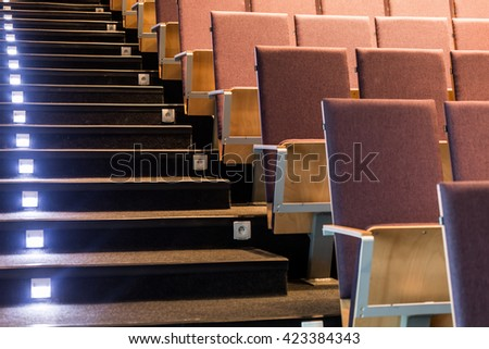 Auditorium with stairs,led lighting and rows of wood chairs - stock photo