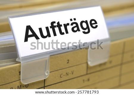 Auftraege printed on file folder in german language - orders - stock photo