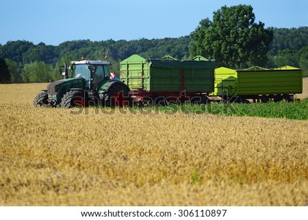 August 13, 2015, Germany near the town Dassow: tractor with two trailers at harvest on a wheat field, agricultural scene in rural area - stock photo