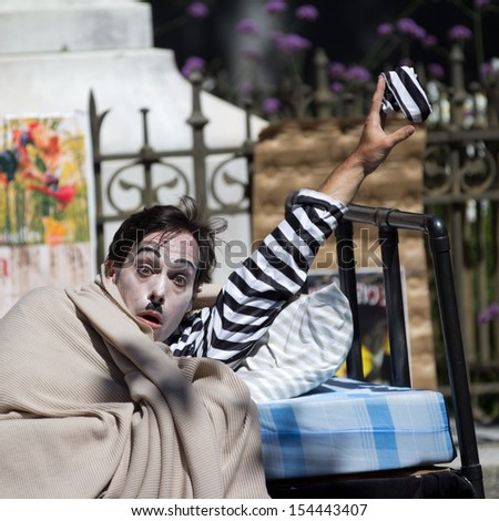 AURILLAC, FRANCE - AUGUST 21: a clown is showing a striped beret as part of the Aurillac International Street Theater Festival, Company Les hommes papillon,on august 21, 2013, in Aurillac,France  - stock photo