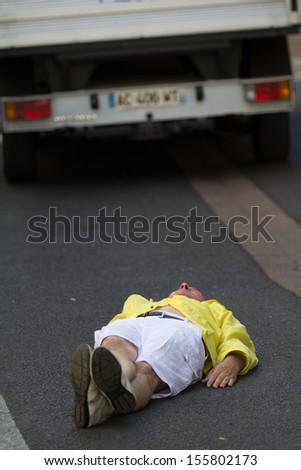AURILLAC, FRANCE - AUGUST 22: a comedian  is lying on the road as part of the Aurillac International Street Theater Festival, Cie Groupe Bernard Menaut,on august 22, 2013, in Aurillac,France  - stock photo