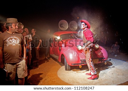 AURILLAC, FRANCE - AUGUST 22: a cowboy arrives in a red car under a big top as part of the Aurillac International Street Theater Festival, Company Off ,on august 22, 2012, in Aurillac,France. - stock photo