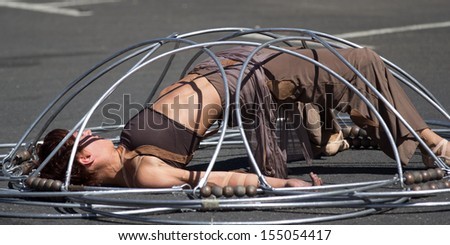 AURILLAC, FRANCE - AUGUST 22: a dancer is locked inside a metallic structure as part of the Aurillac International Street Theater Festival, Company Eclektic,on august 22, 2013, in Aurillac,France  - stock photo