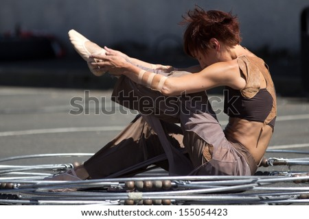 AURILLAC, FRANCE - AUGUST 22: a dancer sits down in the middle of a metallic structure as part of the Aurillac International Street Theater Festival,Cie Eclektic,on august 22,2013, in Aurillac,France  - stock photo