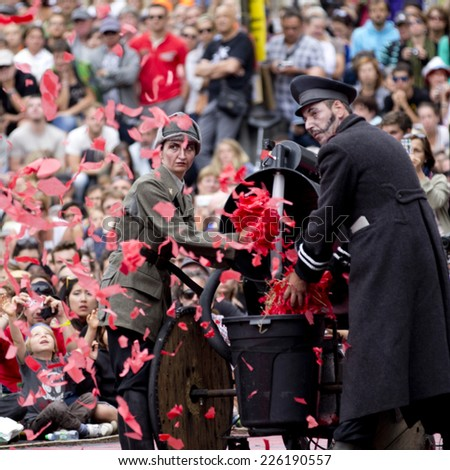 AURILLAC, FRANCE-AUGUST 22: a machine throws up big red confetti as part of the Aurillac International Street Theater Festival, cie teatro del silencio there august 22, 2014 in Aurillac, France. - stock photo