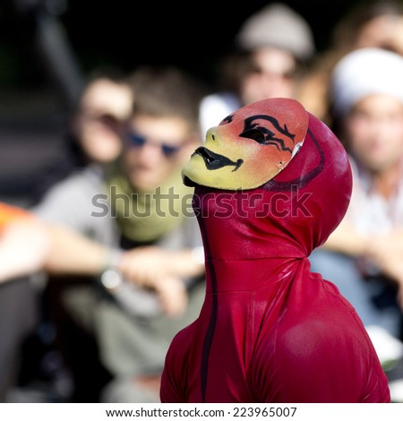AURILLAC, FRANCE-AUGUST 25: a masked man wearing red clothes looks up as part of the Aurillac International Street Theater Festival, cie Bakhus 24,on august 25, 2014, in Aurillac,France.  - stock photo