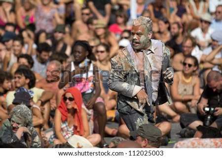 AURILLAC, FRANCE - AUGUST 22: a very dirty actor is sticking out his tongue as part of the Aurillac International Street Theater Festival, Company n�°8 ,on august 22, 2012, in Aurillac,France. - stock photo