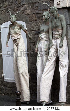 AURILLAC, FRANCE - AUGUST 23: actors walking on stilts as part of the Aurillac International Street Theater Festival, on august 23, 2012, in Aurillac,France. - stock photo